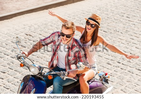 Having great fun together. Top view of beautiful young couple riding scooter together while happy woman keeping arms outstretched and smiling  - stock photo