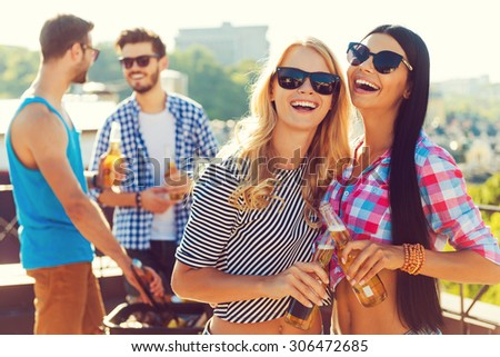 Having great time together. Two cheerful young women clinking glasses with beer and smiling while two men barbecuing in the background - stock photo