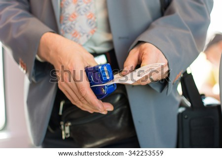 having her ticket checked by the train conductor puncher for tickets - stock photo