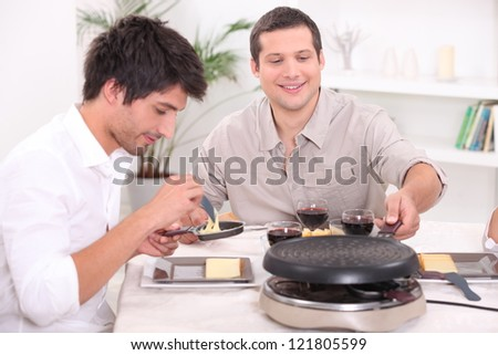 Having raclette for dinner - stock photo
