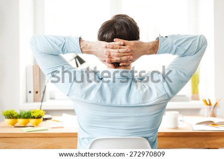 Having rest for productive work. Rear view of young man in shirt holding head in hands while sitting at his working place - stock photo