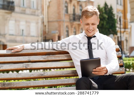 Having rest. Smiling attractive businessman sitting on bench and using new tablet.
