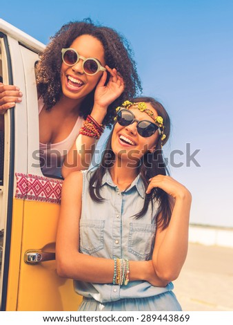 Having so much fun together. Cheerful young woman leaning at the retro mini van while young African woman looking at camera through the vehicle window - stock photo