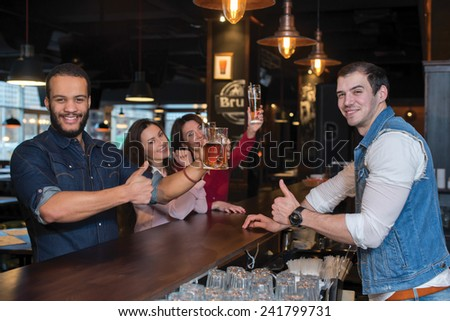Having some fun with beer. Portrait of young and handsome afro american guy. He is standing at the bar counter and showing his beer. His female friends are standing with beer on the background