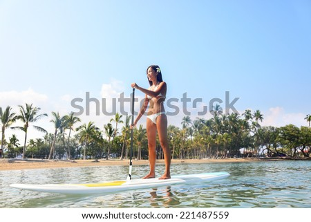 Hawaii beach lifestyle woman paddleboarding in bikini.on SUP. Beautiful multiethnic woman surfing on stand up paddleboard on Big Island, Hawaii. Multiracial Asian Caucasian girl. - stock photo