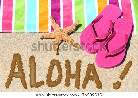 Hawaii beach travel concept. ALOHA text written in sand with water next to beach towel and summer sandals and starfish. Hawaiian vacation holidays background. - stock photo