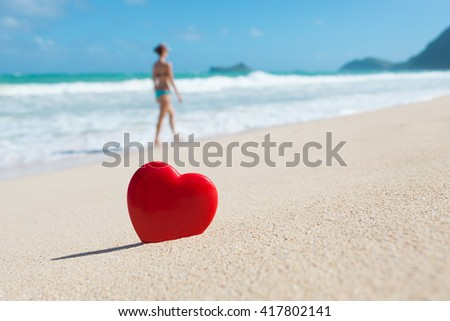 Hawaii beach vacation. Focus on heart in the sand with young woman walking in the distance.  - stock photo