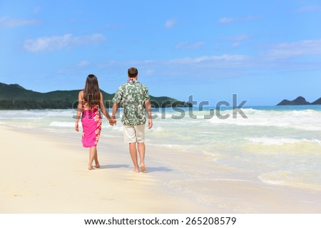 Hawaii honeymoon couple of newlyweds walking on tropical beach in Hawaiian apparel, pink sarong dress and green Aloha shirt for Polynesian cultural tradition. Young people holding hands happy in love. - stock photo