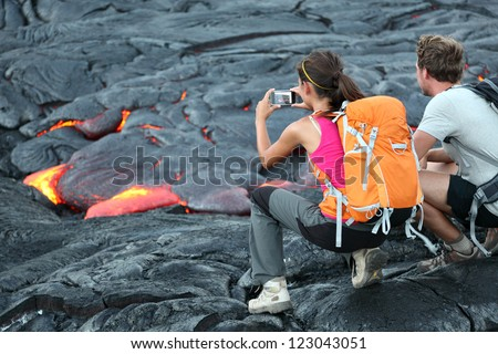 Hawaii lava tourist. Tourists taking photo of flowing lava from Kilauea volcano around Hawaii volcanoes national park, USA. - stock photo
