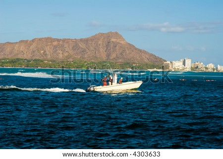 Hawaii's famous Diamond Head crater with a fishing boat passing in front - stock photo