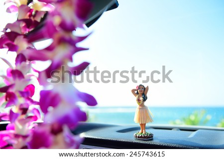 Hawaii travel car - Hula girl dancing on dashboard and lei during road trip. - stock photo