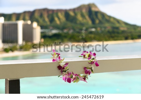 Hawaii travel icon: Lei flower necklace in front of Waikiki beach and Diamond Head state monument in Honolulu - stock photo
