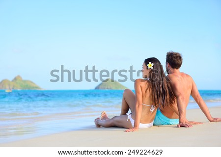 Hawaii vacation couple relaxing tanning on beach. Beautiful young adults on holidays lying down on white sand of Lanikai beach, Oahu island, Hawaii, USA. - stock photo