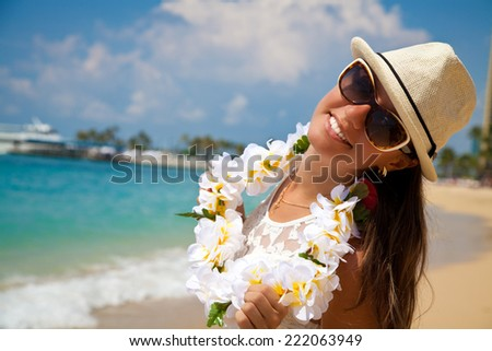 Hawaii woman with flower lei garland of white plumeria. Beautiful smiling  woman in white on beach  on the hawaiian Honolulu island . - stock photo