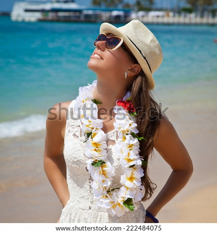Hawaii woman with flower lei garland of white plumeria. Beautiful smiling woman in white on beach on the hawaiian Honolulu island. - stock photo