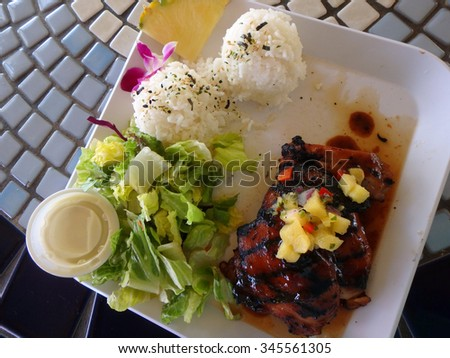 Hawaiian BBQ Chicken Plate guava marinated, pineapple-pepper sauce, White Rice, Pineapple slice, flower, and Salad with side of dressing on square white plate on a table. - stock photo