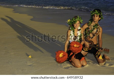 hawaiian hula couple on the beach at sunrise with the man playing ukulele
