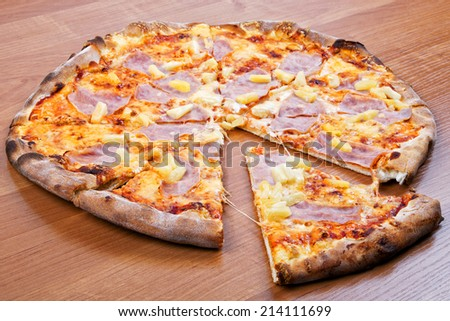 Hawaiian pizza on a wooden background