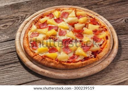 Hawaiian pizza on the old board. - stock photo