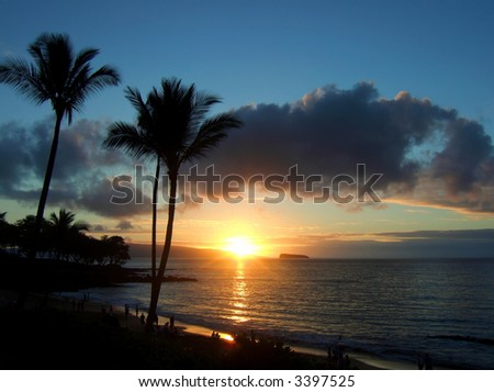 Hawaiian sunset with Molokini Crater in the distance. - stock photo
