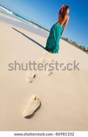 Hawaiian woman walking at the beach leaving footprints on the sand - stock photo