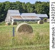 Hay bales around a rustic barn with a steel roof. - stock photo