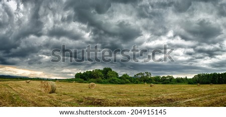 Hay bales in a dramatic sky - stock photo