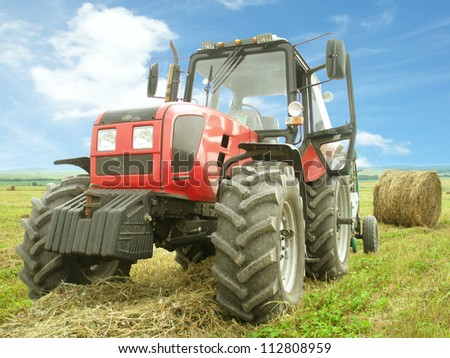 Hay harvesting in the field by means of a tractor - stock photo