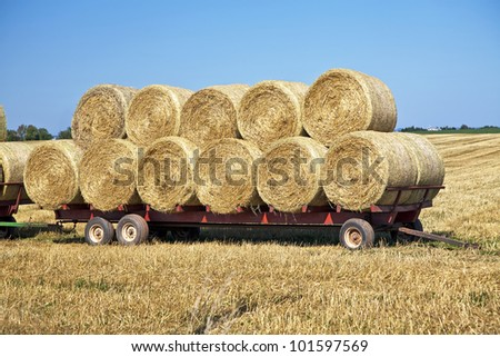 Hay wagon loaded with round bales of straw in rural Prince Edward Island, Canada. - stock photo