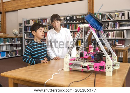 HAYDEN, IDAHO - JUNE 7, 2014. Two children watch the 3D printer making an object at the Hayden Library n Hayden, Idaho on June 7 2014. - stock photo