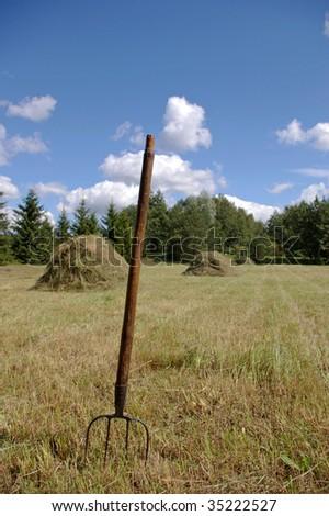 hayfork and haystacks on field - stock photo