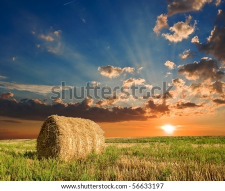 haystack in a field by a sunset - stock photo