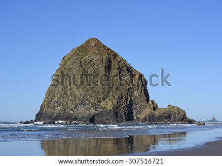 Haystack Rock, Cannon Beach, Oregon, with blue sky in the background and reflections in wet sand in the foreground. A small warning sign was edited out.   - stock photo