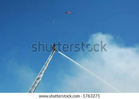 Hayward fireman fighting a fire with a news helicopter overhead - stock photo