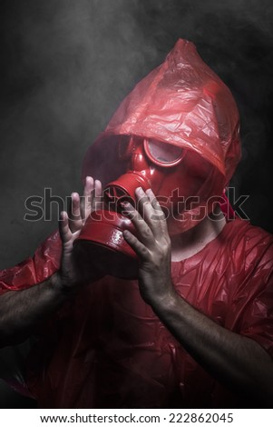 Hazard, A man in a gas mask over  the smoke. black background and red colors - stock photo