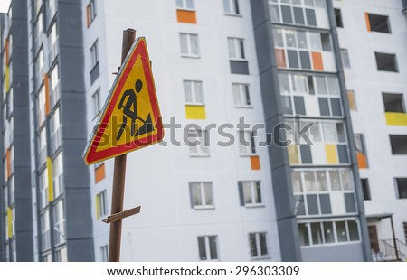 Hazard warning attention sign man with shovel. Symbol of road construction near new house construction Empty space for inscription  - stock photo