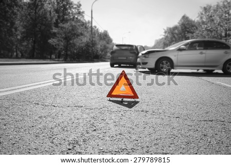 Hazard warning triangle laid out on the road  behind two crashed cars, black and white photo with a  red accent on a triangle - stock photo