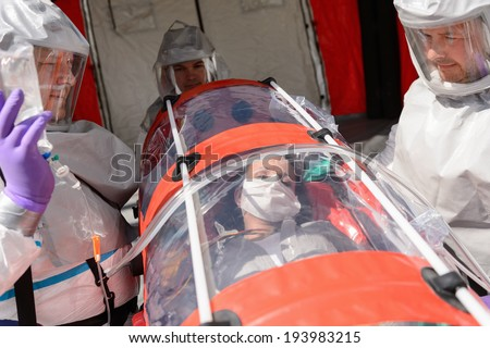 Hazardous material team with patient on stretcher outdoors - stock photo