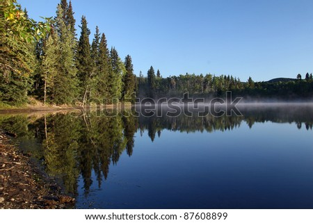 Haze above water, reflection of trees in small lake - stock photo
