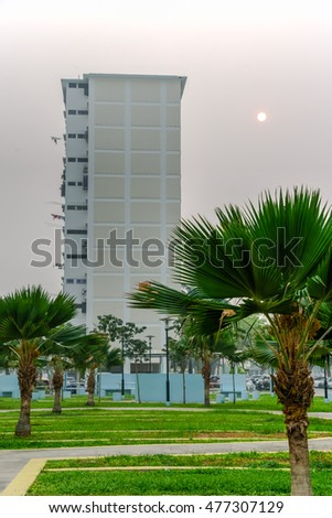 Haze fills the residential complex during sunrise, grass courtyard, trees, drying hanging clothes, dense apartments in Singapore. Haze caused by the forest fire and burning of plantation in Indonesia.