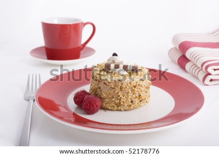 Hazelnut cake topped with cream and garnished with raspberries on a red plate.
