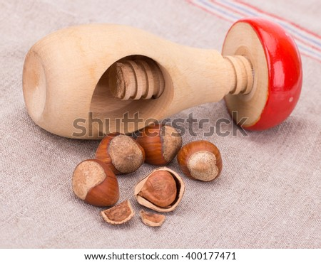 Hazelnut or filbert nut with nut cracker isolated on tissue background cutout - stock photo