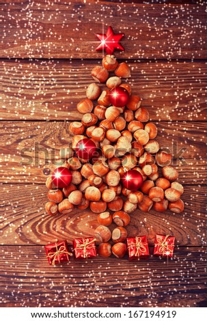 Hazelnuts, filbert on old wooden background. Christmas tree made of hazelnuts on a wooden surface - stock photo