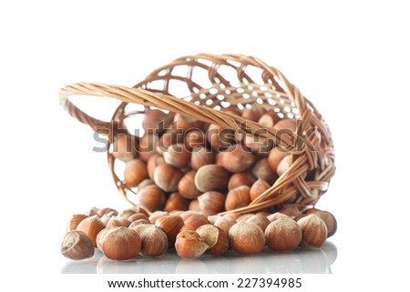 hazelnuts in a wicker basket on a white background - stock photo