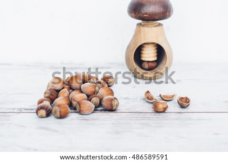 Hazelnuts in pile on wooden table with one nut in mushroom-shaped nut-cracker and one nut cracked open