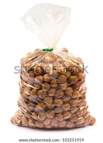 Hazelnuts in plastic bag on white background - stock photo