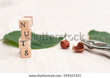 Hazelnuts on a wooden background with leaves and nutshell. Walnut word from wooden blocks. - stock photo