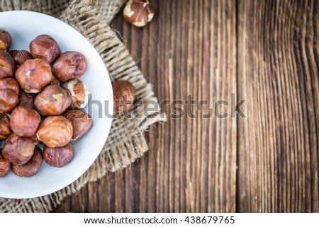 Hazelnuts on vintage wooden background (selective focus; close-up shot) - stock photo