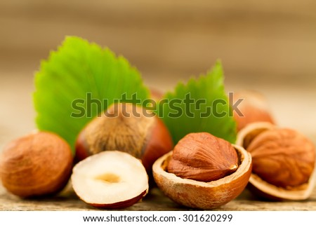 hazelnuts with leaves on old wooden background. Healthy vegetarian food - stock photo