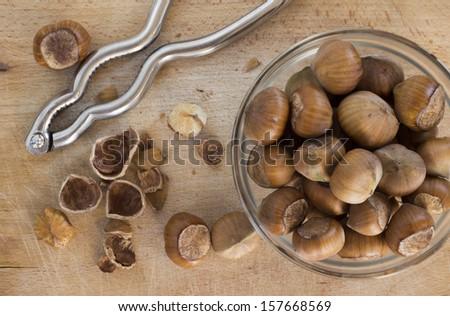 Hazelnuts with nutcracker on the wooden board - stock photo